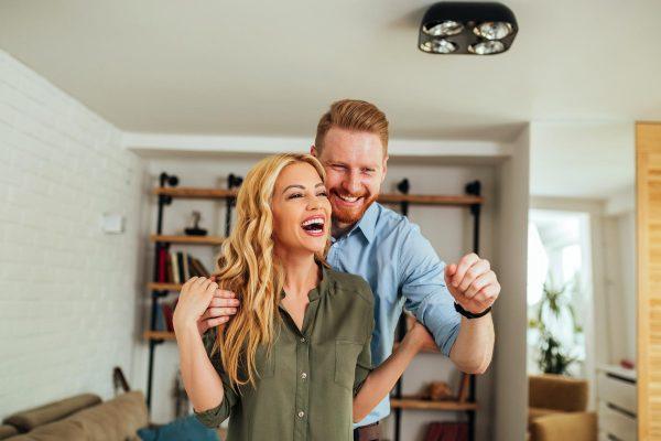 Paar-freut-sich-pber-neue-Wohnung-im-Wohzimmer